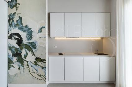 Fold-away kitchen behind handpainted kerlite panels